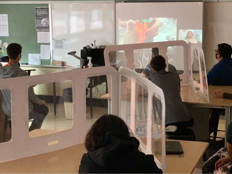 Students watch a background video